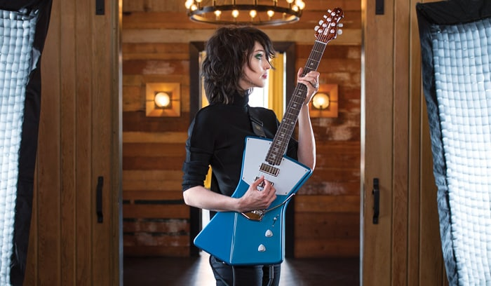 St. Vincent stands with her signature Ernie Ball Music Man electric guitar