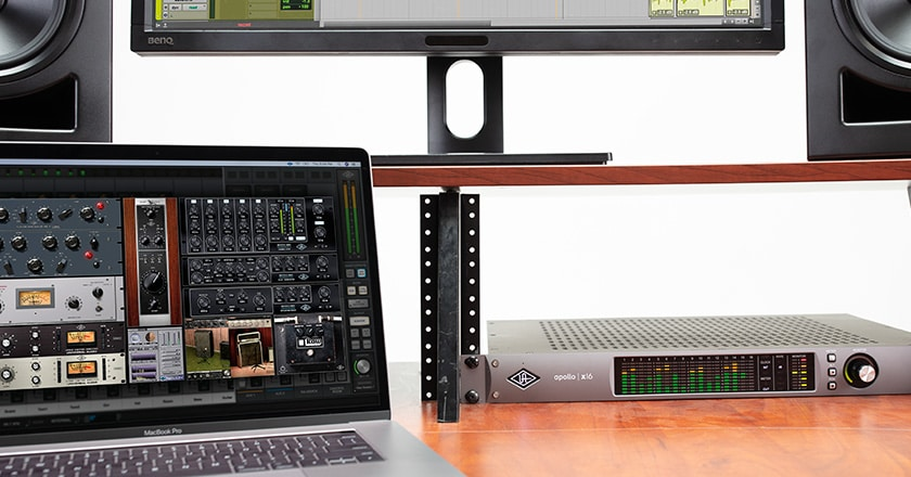 Apollo x16 rackmounted on a desk with UAD plugins on a laptop screen