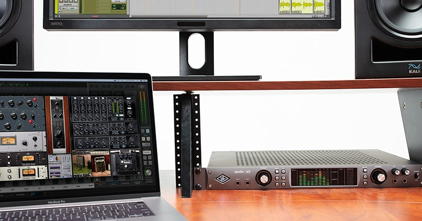 Apollo x8 rackmounted on a desk with UAD plugins on a laptop screen