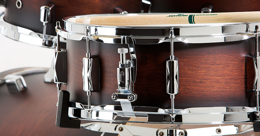 Pearl Decade Maple snare drum with matching finish, sticks resting on top, chrome throw-off visible, toms and cymbals in background