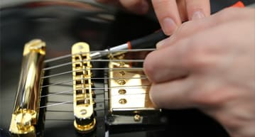 person aligning guitar strings